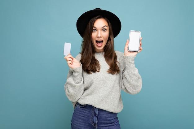 Attraktive erstaunte junge brünette frau mit schwarzem hut und grauem pullover einzeln auf blauem hintergrund mit kreditkarte und handy mit leerem display für modell mit blick in die kamera.