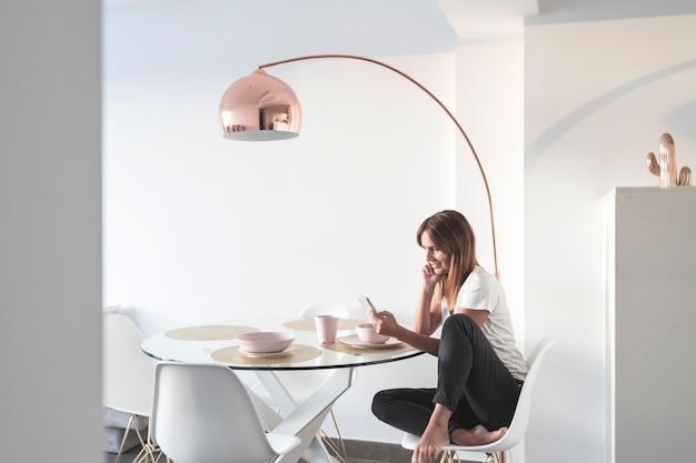 Attraktive erwachsene frau, die im wohnzimmer sitzt, während sie handy verwendet