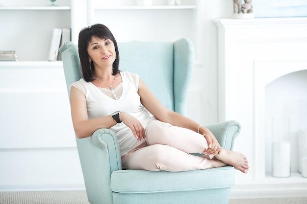 Attraktive erwachsene frau, die zuhause auf der couch sitzt. schöne mittelalterfrau zu hause.