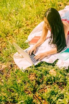 Attraktive ethnische frau, die laptop in der wiese verwendet