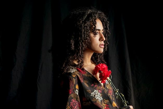 Attraktive ethnische frau mit roten blumen in der dunkelheit