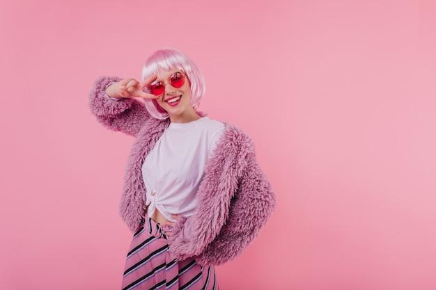 Attraktive europäische dame trägt stilvolle brille und perücke. innenaufnahme des lächelnden entzückenden mädchens in der rosa pelzjacke
