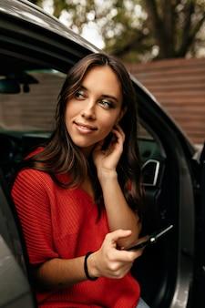 Attraktive europäische frau, die roten pullover trägt, der im auto mit smartphone sitzt und lächelt