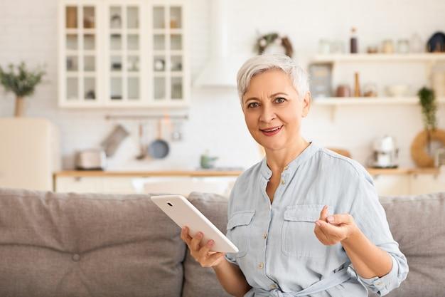 Attraktive europäische rentnerin, die drahtlose hochgeschwindigkeits-internetverbindung genießt, sich zu hause entspannt, auf der couch mit dem elektronischen gerät des digitalen touchpads sitzt und mit einem lächeln schaut