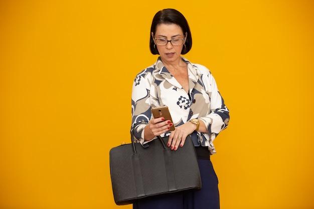 Attraktive fällige geschäftsfrau, die mit ihrem handy arbeitet
