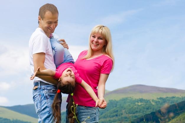 Attraktive familie, die spaß in einem sommer auf berg hat