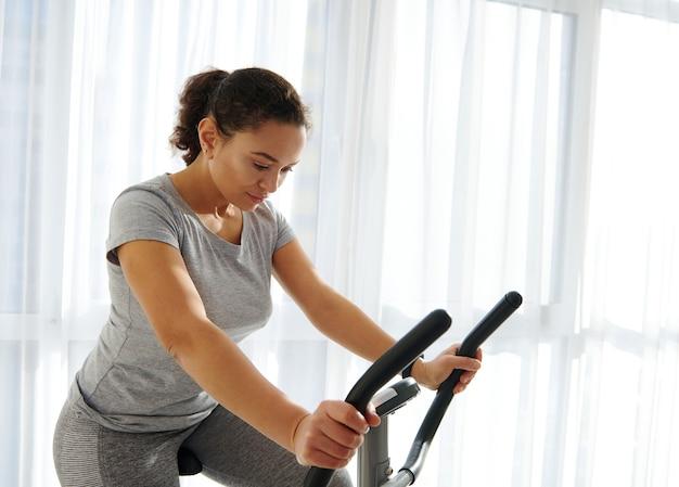 Attraktive fit frau, die auf einem stationären fahrrad zu hause an einem schönen sonnigen tag trainiert