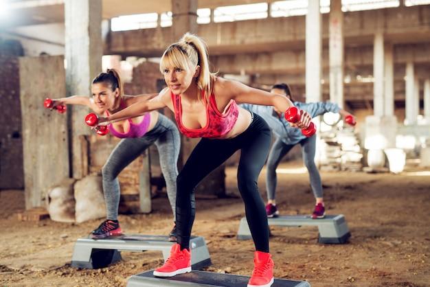 Attraktive fitness-mädchen, die step-aerobic außerhalb des fitnessraums mit hanteln ausüben.
