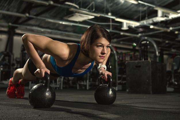 Attraktive fitnessfrau, die liegestütze mit auf gewichten tut