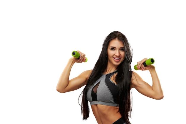 Attraktive fitnessfrau, die mit hanteln arbeitet. porträt lokalisiert auf einem weißen hintergrund.