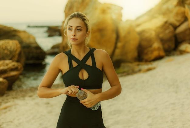Attraktive fitnessfrau in sportkleidung hält eine flasche wasser an einem wilden strand.