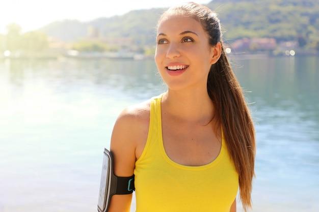 Attraktive fitnessfrau mit armband für smartphone, das zur seite den kopierraum mit morgensonnenlicht und see auf dem hintergrund schaut.