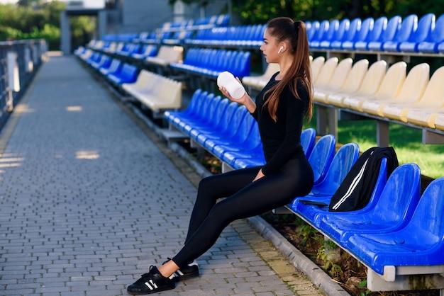Attraktive fitnessfrau mit einer flasche mischt sporternährung oder protein, während sie an der stadiontribüne in einer pause zwischen schweren trainings sitzt.