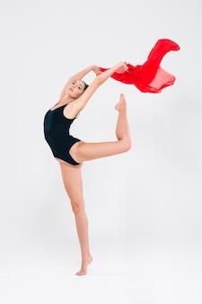 Attraktive flexible turnerin lokalisiert auf einer weißen wand