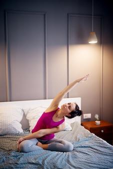 Attraktive form sportliche frau mittleren alters, die sitzende yoga-posen auf dem bett vor dem schlafengehen tut.
