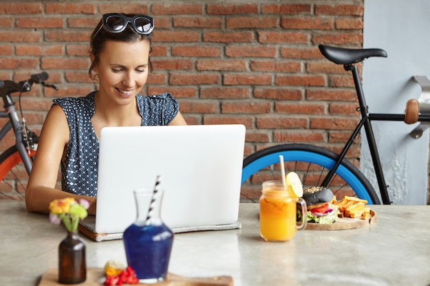 Attraktive fotografin, die bilder mit bildbearbeitung retuschiert, zu mittag isst und vor einem generischen laptop sitzt. studentin, die online auf notizbuch studiert