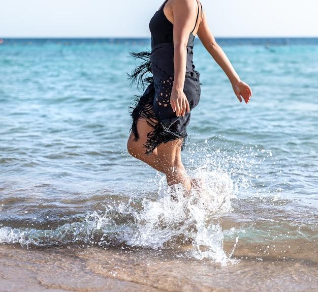 Attraktive frau am meer macht ihre füße im wasser nass.