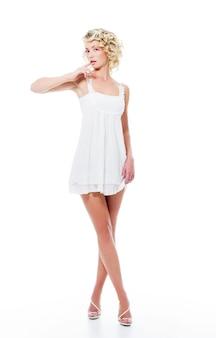 Attraktive frau der modesinnlichkeit mit dem modernen weißen kleid, das im studio aufwirft