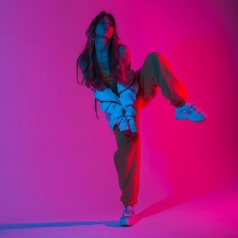 Attraktive frau des models in einem stylischen jugendsportanzug in trendigen turnschuhen steht auf einem bein im studio mit hellrosa licht. mädchentänzer, der auf dem hintergrund eines farbigen studios tanzt.