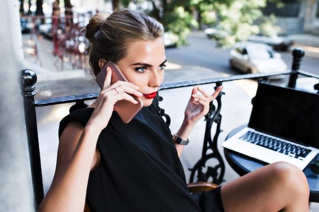 Attraktive frau des nahaufnahmeporträts im schwarzen kleid, das am telefon auf der terrasse spricht. sie schaut zur seite.