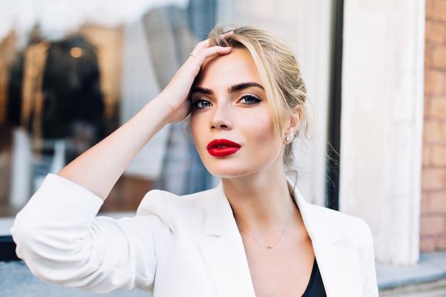 Attraktive frau des nahaufnahmeporträts mit roten lippen auf straße. sie berührt haare und schaut in die kamera.
