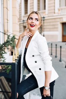 Attraktive frau des porträts in der weißen jacke, die auf zaun auf straße lehnt. sie lächelt zur seite.