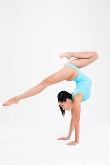 Attraktive frau, die akrobatischen stunt lokalisiert auf einer weißen wand tut
