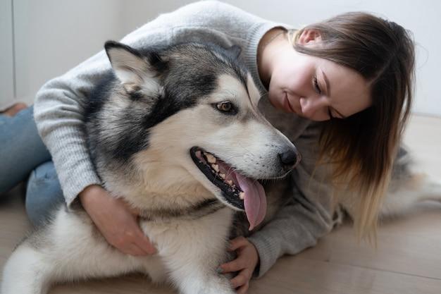 Attraktive frau, die alaskischen malamute-hund auf dem boden umarmt.