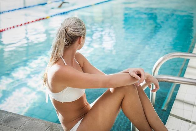 Attraktive frau, die am rand des pools sitzt