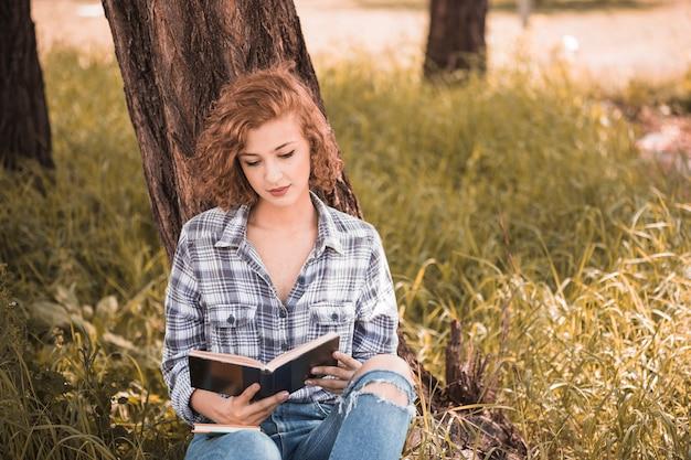 Attraktive frau, die auf baum- und lesebuch sich lehnt