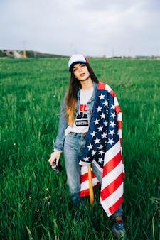 Attraktive frau, die auf dem gebiet mit amerikanischer flagge bleibt