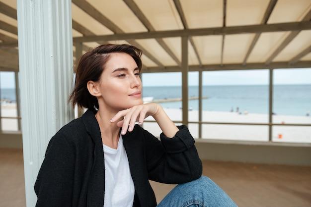 Attraktive frau, die auf der terrasse am strand sitzt und sich entspannt
