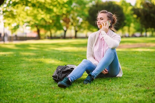 Attraktive frau, die auf handy in einer angenehmen atmosphäre draußen im park späht