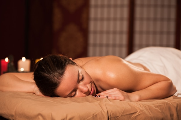 Attraktive frau, die auf massagetabelle in der badekurortmitte, exemplarplatz liegt. junger weiblicher kunde, der auf ihre entspannende ganzkörpermassage, tag am verwöhnungssalon verbringend wartet. erholung, gesundheit, entspannung