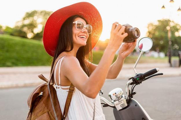 Attraktive frau, die auf motorrad in der straße, sommerferienart reist, reist, lächelt, spaß hat, stilvolles outfit, abenteuer, fotos auf vintage-fotokamera macht, lederrucksack trägt
