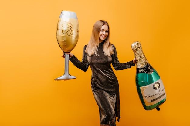 Attraktive frau, die auf orange mit flasche champagner tanzt. innenporträt der scherzhaften kaukasischen frau, die geburtstag mit wein feiert.