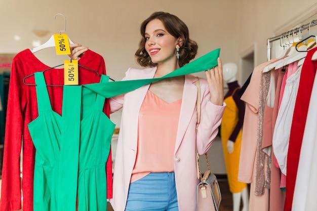 Attraktive frau, die bunte kleider auf kleiderbügel im bekleidungsgeschäft hält