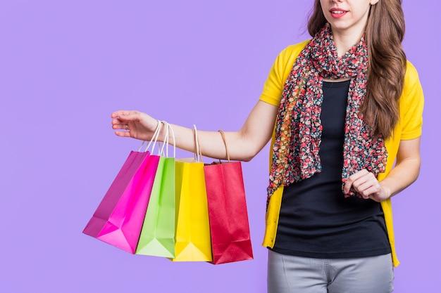 Attraktive frau, die bunte papiertüte gegen purpurroten hintergrund trägt
