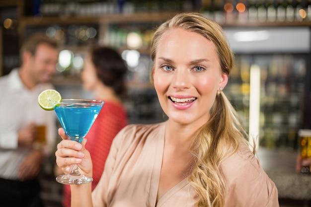 Attraktive frau, die das cocktailglas gegenüberstellt kamera hält