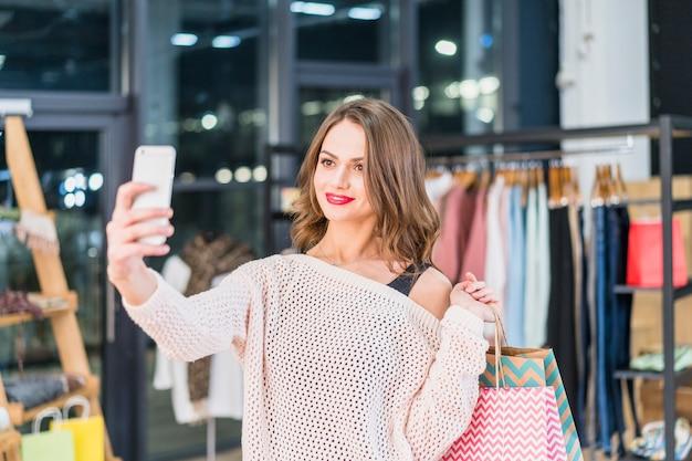 Attraktive frau, die das selfie hält einkaufstaschen nimmt
