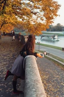 Attraktive frau, die draußen smartphone im park verwendet