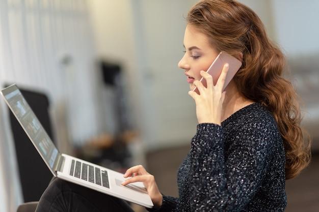 Attraktive frau, die durch das smartphone anruft, das am computer arbeitet. junge frau mit handy und laptop.
