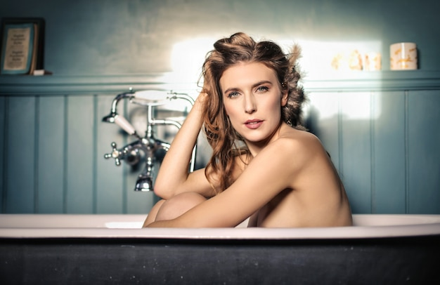 Attraktive frau, die ein bad in einer antiken badewanne hat
