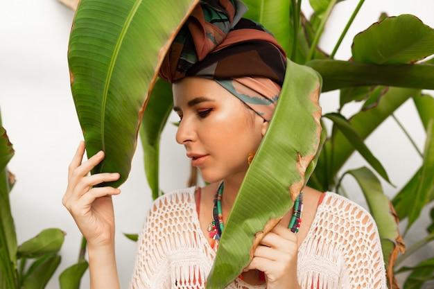 Attraktive frau, die ein buntes kopftuch wie ein turban und große runde ohrringe trägt