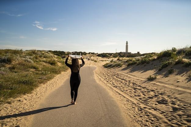 Attraktive frau, die ein surfbrett über ihrem kopf trägt