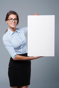 Attraktive frau, die ein weißes plakat hält