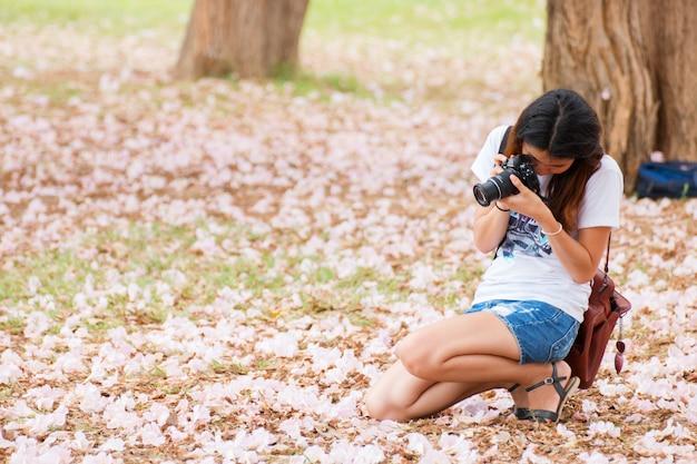 Attraktive frau, die eine fotorosa-blumenblüte macht