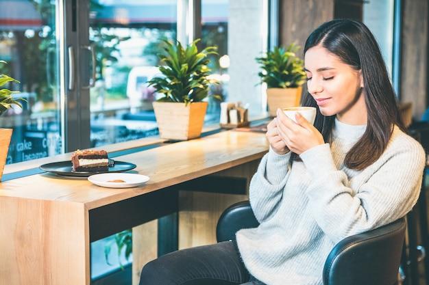 Attraktive frau, die eine tasse kaffee elegant mit geschlossenen augen hält, die durch fenster sitzen