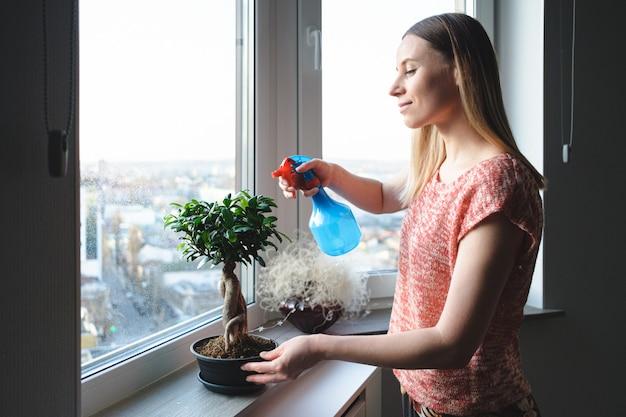 Attraktive frau, die einen bonsai-baum in der wohnung wässert