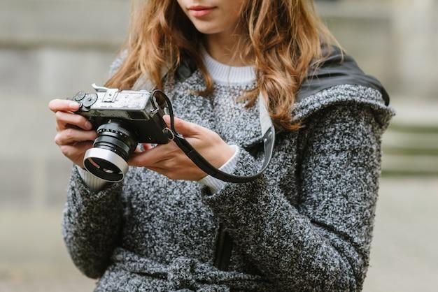 Attraktive frau, die einen grauen mantel trägt, der eine weinlesekamera hält und es betrachtet
